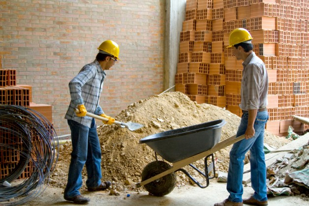 Happy construction workers wearing helmets and working - teamwork concepts